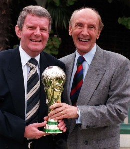 BBC sports presenters John Motson (left) and Barry Davies hold up a plastic copy of the coveted World Cup during a photocall in London today (Thursday) to promote the BBC's coverage of the forthcoming event, 'The World Cup Experience.' Photo by John Stillwell/PA